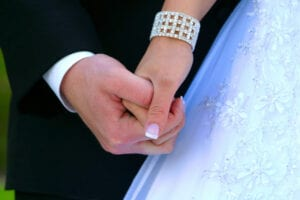 Bride and Groom Clasp Hands